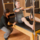 Student being instructed by staff member at pilates studio Mindful Movements