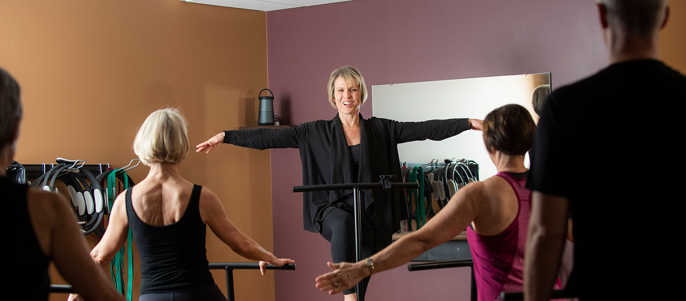 Pilates teacher guiding her students